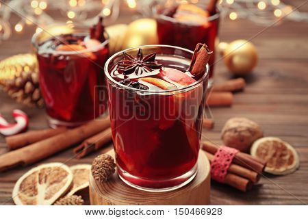 Glass of delicious Christmas mulled wine  on wooden stand, closeup