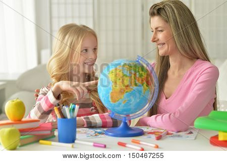 portrait of mother helping her little daughter with homework