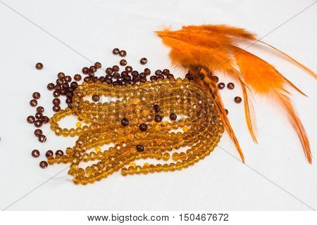 Beautiful colored glass beads and thread beads. feathers on white background