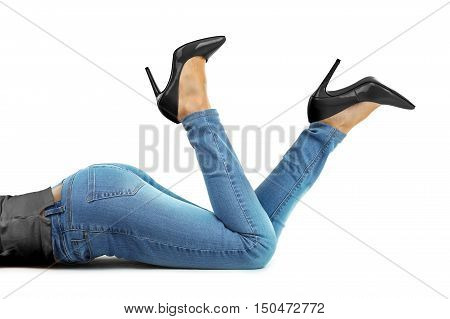 Woman with blue jeans and high heels laying on the floor of the studio.