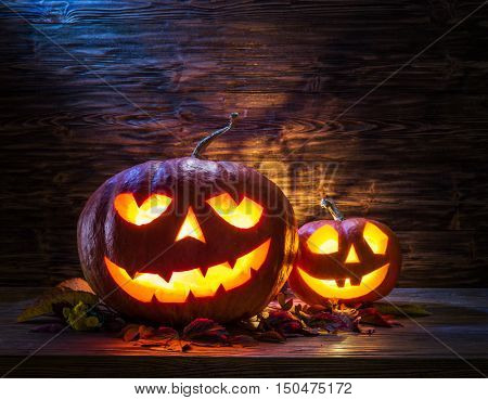 Halloween pumpkin lantern or jack-o'-lantern is one of the symbols of Halloween. Halloween attribute. Wooden background.