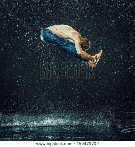 The male break dancer in water on dark background.