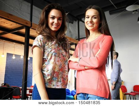 Two female collegues standing next to each other in an office