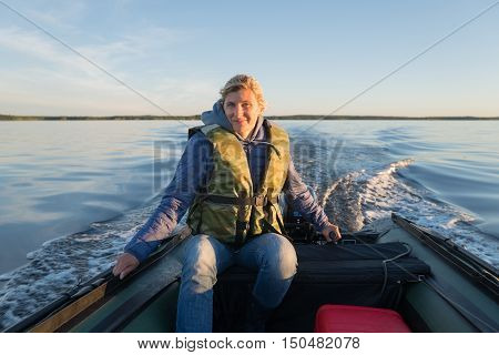 Wonderful woman is operating of boat on the sea