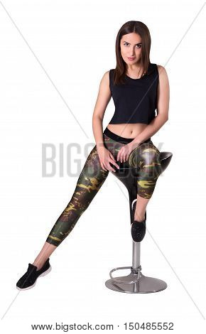 Fashionable beautiful young woman on a bar stool. Sport girl posing on barstool. isolated on white background