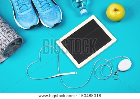 Fitness background made of sneakers, mat, bottled water, apple measuring tape and clean chalkboard on blue background. Concept of healthy lifestile, everyday training and force of will.
