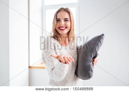 Portrait of a smiling woman holding pillow with outreached hand at home