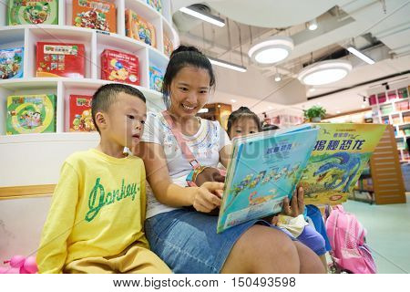 SHENZHEN, CHINA - SEPTEMBER 09, 2016: woman with children read book at a store in Shenzhen. Shenzhen is a major city in Guangdong Province, China.