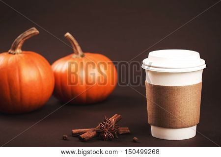 Paper cup of coffee to take away with spices and pumpkin. Concept of autumn spicy latte. Place for text or logo on brown coffee holder.