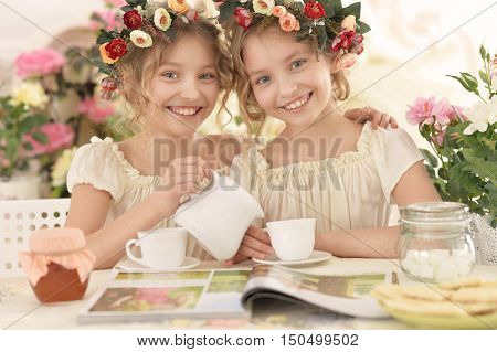 Cute  tweenie girls  in wreaths with magazine and tea  at home