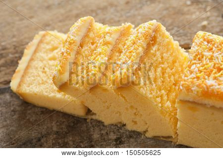 Close up of yellow cake with sprinkles and icing sliced into small portions on a rustic wood table