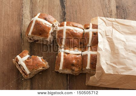 Fresh square hot cross buns sticking out of paper bag