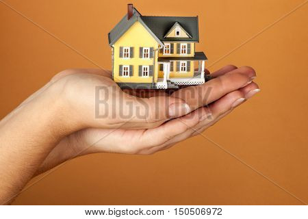 Women's Cupped Hands Holding a Model of a House on Orange Background