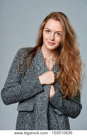 Happy smiling beautiful woman muffling in warm knitted cardigan, over gray background