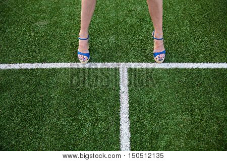 Woman legs in high heel sandals on the soccer field near the white line