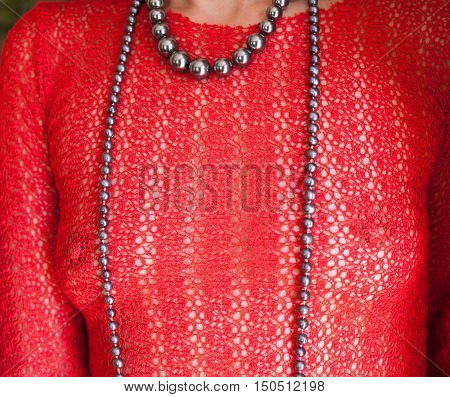 Sexy woman in the red see-through blouse and long necklace.