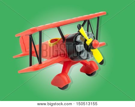 Red aircraft toy isolated on green background