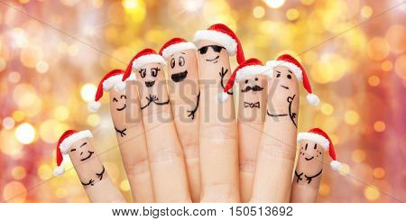 family, holidays, christmas and body parts concept - close up of fingers with smiley faces and santa hats over lights background
