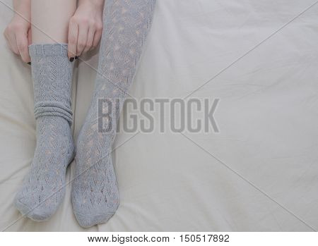Woman puts on grey socks sitting on bed