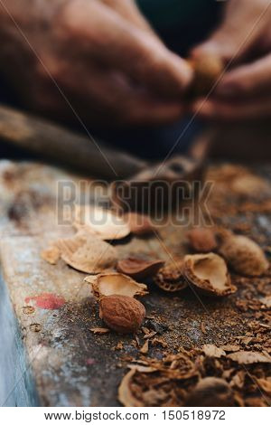 closeup of a pile of shelled almonds and its cracked shells, and a man opening some other unshelled almonds with a hammer