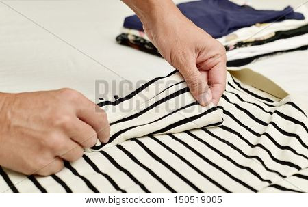 closeup of a young caucasian man folding a polo shirt, with a pile of folded clothes in the background