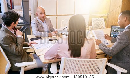 Indoor meeting between 4 business executives in a warm creative environment, making use of tech and documents during the early hours of the morning in preparation for the coming week.