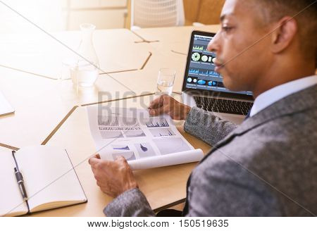 Over the shoulder view of a professional business executive holding a printed document with charts and graphs on it as well as a computer screen with graphics on as well.
