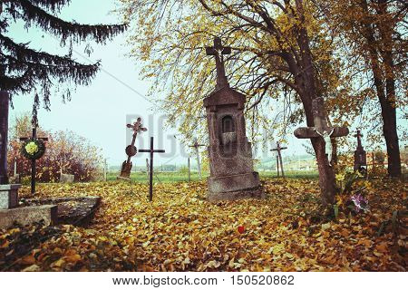 Scary leaning cross tomb stones in a foggy autumn scene in fall. Old creepy graves on cemetery in Slovakia. Spooky aged tombstones on grave yard with trees, leaves on the ground in All Saints' Day