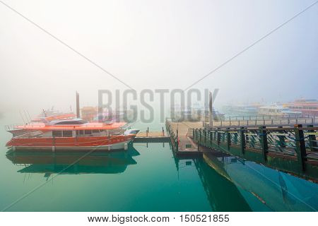 SUN MOON LAKETAIWAN - MARCH 21: Fog with many boats parking at the pier while sunrise on MARCH 21 2015 at Sun Moon Lake Taiwan. Sun Moon Lake is the largest body of water in Taiwan with nataral place.
