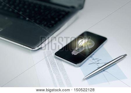 business, technology and statistics concept - close up of smartphone with lightbulb on screen, laptop computer and chart with pen on office table
