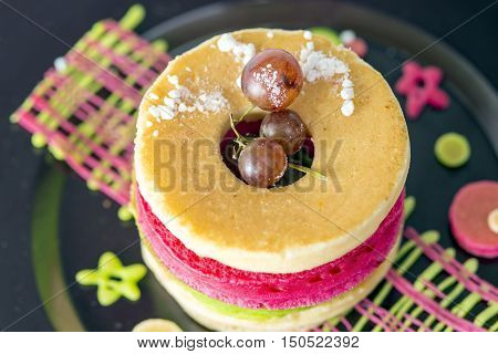Stack of small pancakes with grape on black dish