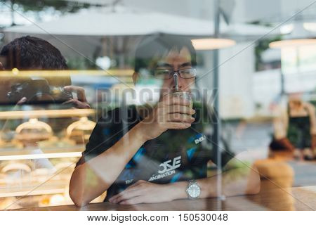 Asian Men  Drinking Coffee  Looking To Ut Side In Cafe