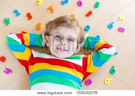 Little blond child with glasses playing with lots of colorful plastic digits or numbers, indoor. Kid boy wearing colorful shirt and having fun with learning math