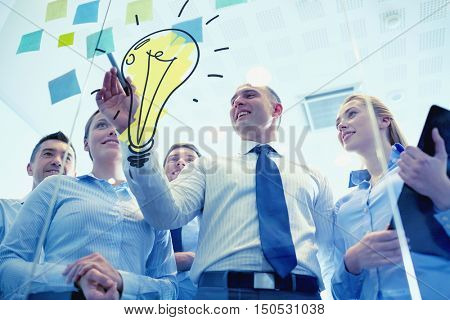 business, people, teamwork and planning concept - smiling business team with marker, stickers and light bulb doodle working in office