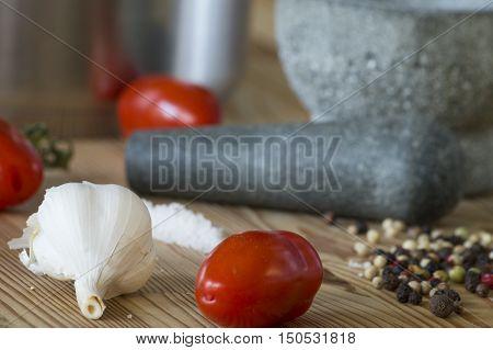 Knoblauch, Tomaten und Mörser auf einer Arbeitsplatte