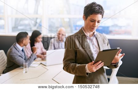 businesswoman holding and using an electronic tablet while standing in front of her business colleagues that are seated at the conference table behind her.