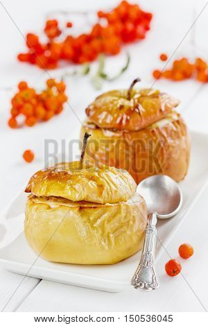 Baked apples with honey, raisins, curds and nuts in a white plate, decorated ashberry on a wooden background. Winter or autumn dessert.