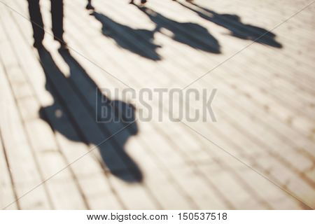 Blurred background of four unrecognizable persons with shadows walking along the pier in Sopot, Poland.