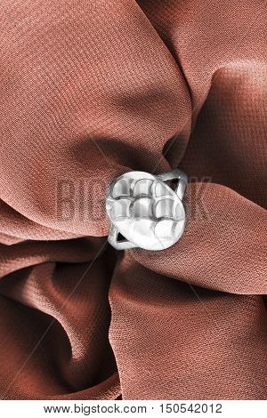 Vintage nacre ring on crumpled brown silk as a background