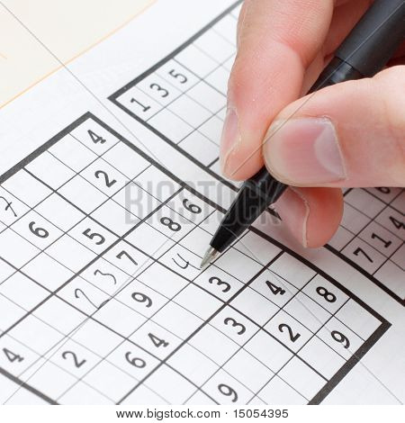 A person solving a sudoku puzzle