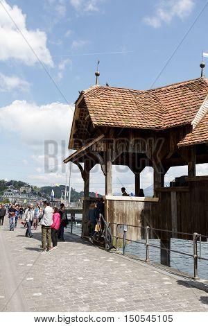 LUCERNE SWITZERLAND - MAY 04 2016: Entry to the roofed wooden Chapel Bridge. This bridge is one of the most recognizable landmarks in the city
