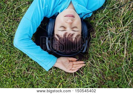 young girl listening to music on headphones. top view. The concept of lifestyle.