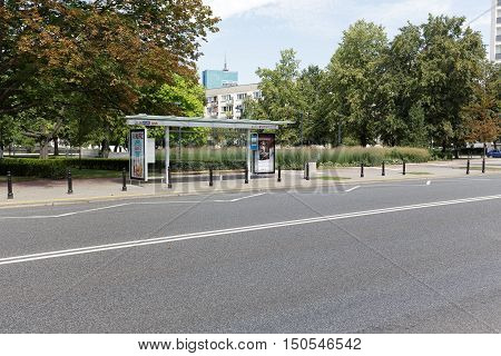 WARSAW POLAND - AUGUST 05 2016: General view towards a street and a covered bus stop where two billboards are placed. This bus stop is empty and waits for passengers or a bus