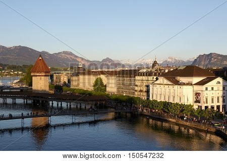 LUCERNE SWITZERLAND - MAY 06 2016: Evening view towards the tower that was built in the river Reuss and is next to the roofed Chapel Bridge. Buildings on the left bank of the river can be seen.