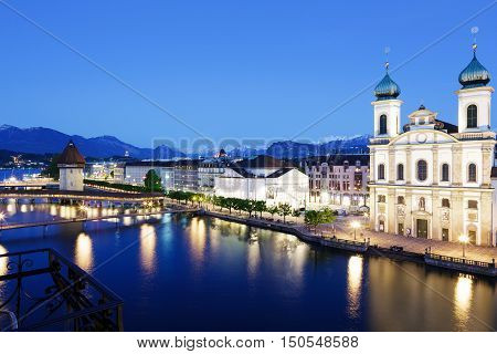 LUCERNE SWITZERLAND - MAY 06 2016: Night view of towards Jesuit Church and made of stone octagonal tower located by the Reuss river in old town. Both buildings are famous tourist attractions.