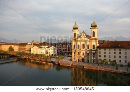 LUCERNE SWITZERLAND - MAY 02 2016: Evening view towards buildings on the left bank of river Reuss. Jesuit Church is one of the most visited tourist attractions in the city