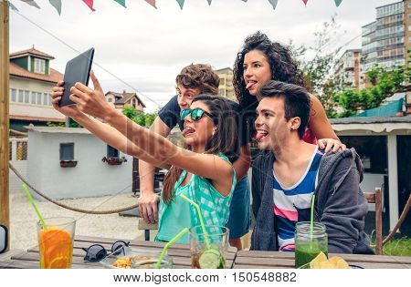 Young happy people sticking out tongues while taking a selfie with a electronic tablet in a summer party. Young people lifestyle concept.
