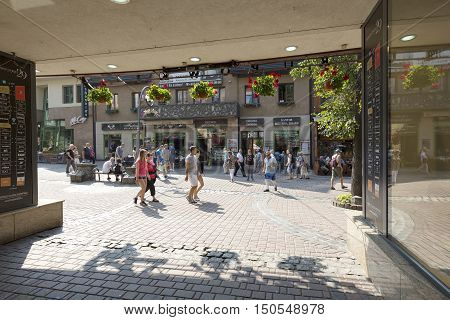 ZAKOPANE POLAND - SEPTEMBER 13 2016: Looking out of the gate many people walking along the street Krupowki can be seen. The Krupowki street it is main shopping area and pedestrian zone in the city