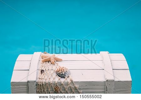 wooden treasure box with mussels in front of blue water
