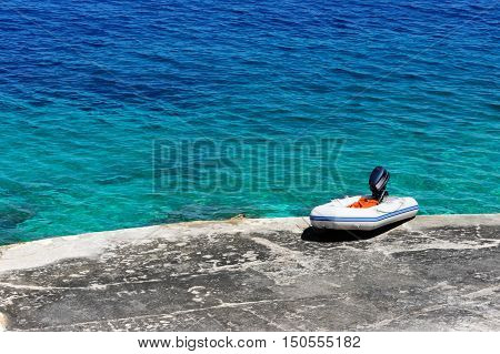 White rubber dinghy with motor on the mediterranean beach
